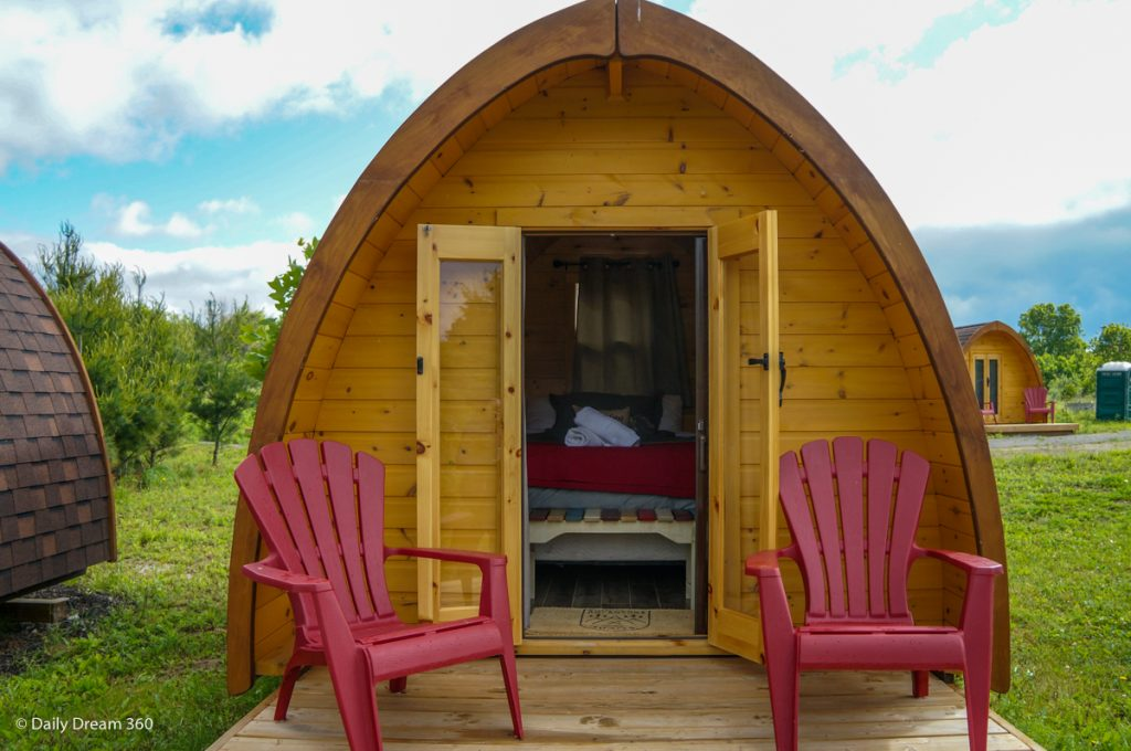 Wilderness Pod with doors open bed inside and two red chairs on deck