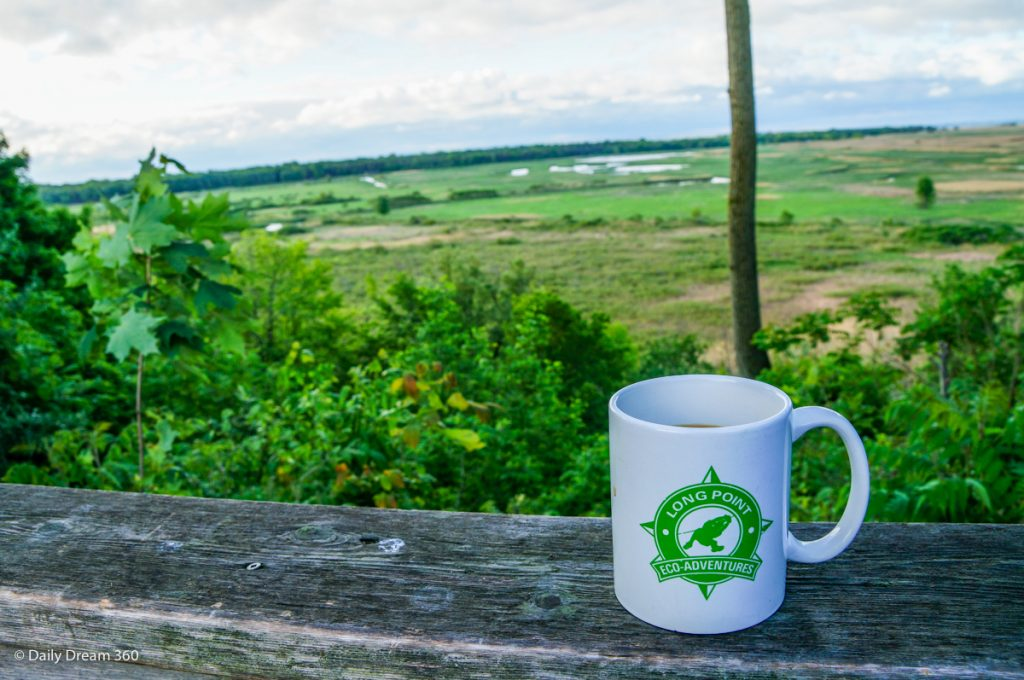 Coffee on wood rail during hike at Long Point Eco-Adventures