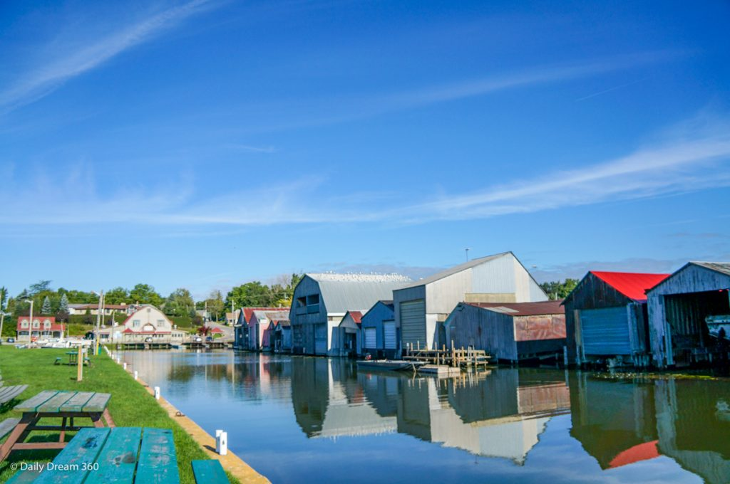 Boat houses reflecting on the water in Port Rowan Ontario