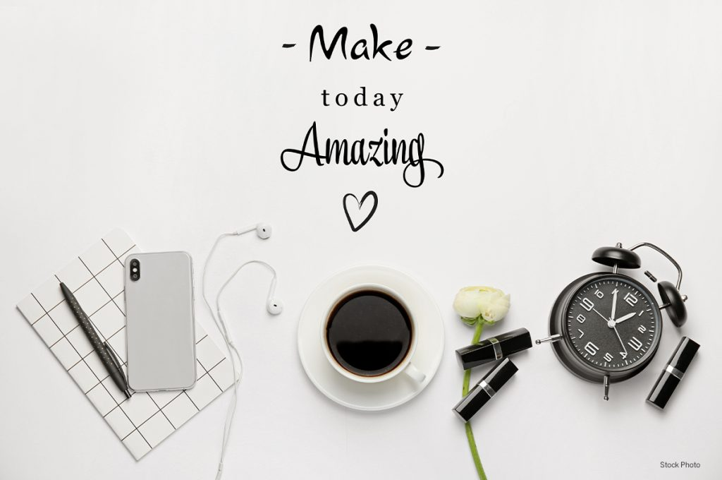desktop with phone, keyboard, coffee and alarm clock and words make today amazing