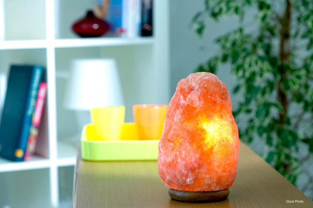 Salt therapy lamp on table with bookcase in background