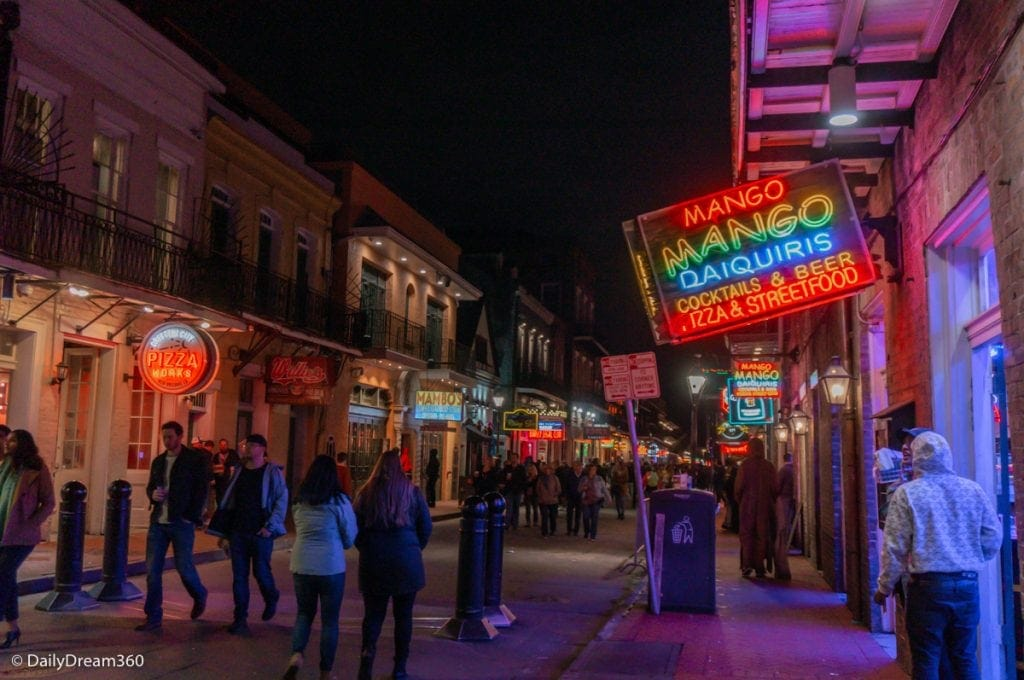Bourbon Street at night with pedestrians walking in street New Orleans