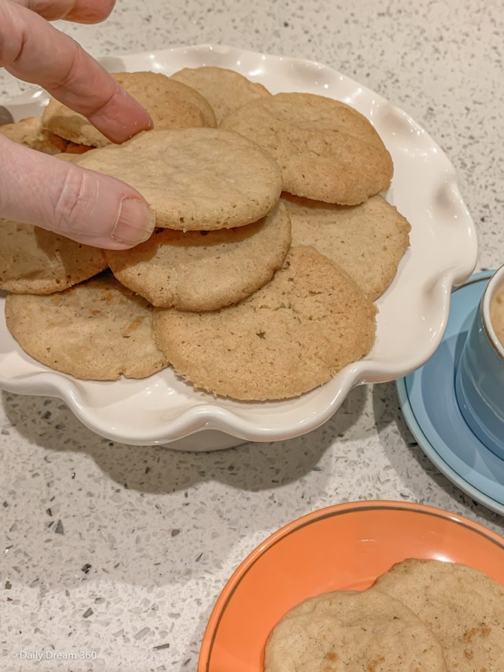 Fingers picking up low carb sugar cookies from plate