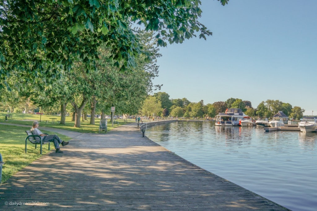 man sitting on bench in front of boardwalk at Orillia Ontario waterfront