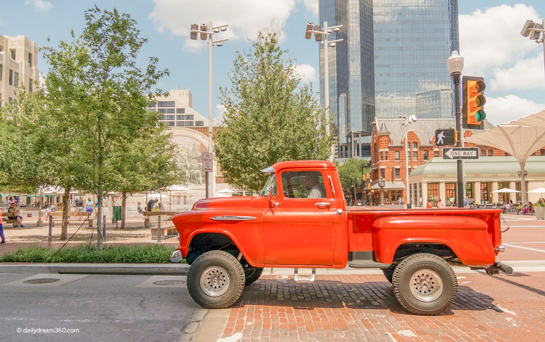 Red truck drive by Sundance square in this image for A Guide of Fun Things to do in Fort Worth Texas