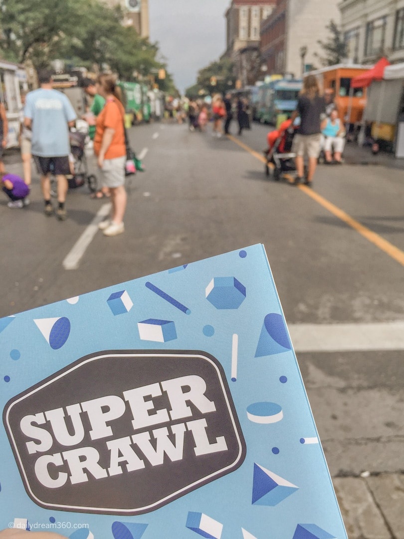 Super Crawl flyer held up with street view in Hamilton Ontario