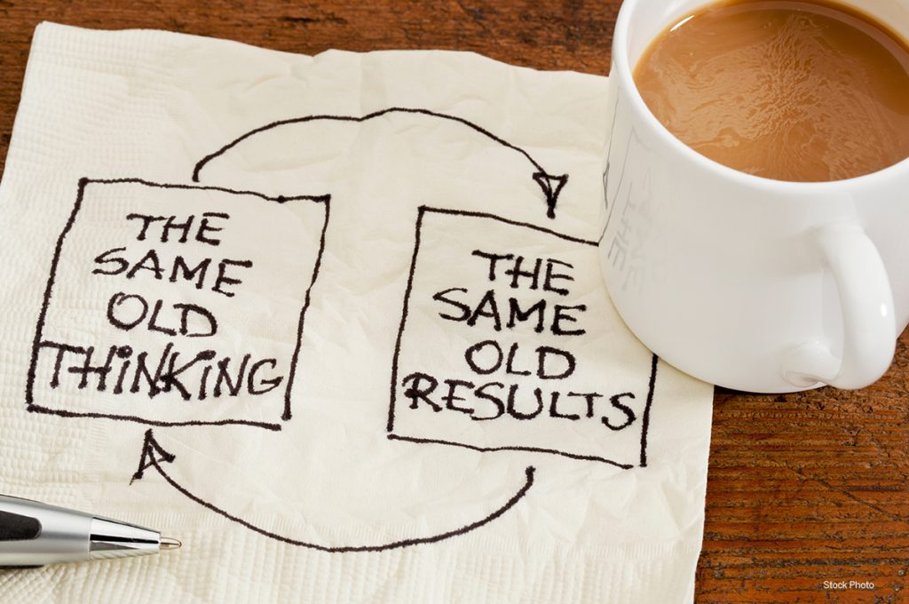 napkin with message same old thinking same old results next to coffee cup
