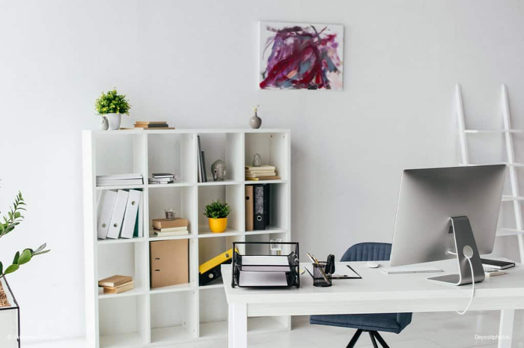 White office desk and bookcase behind it