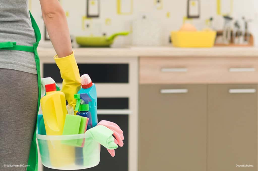 Woman holding cleaning supplies in kitchen