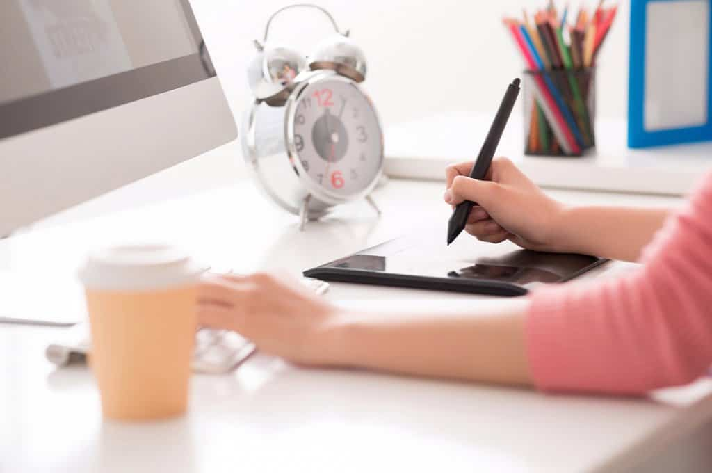 women working at desk with tablet