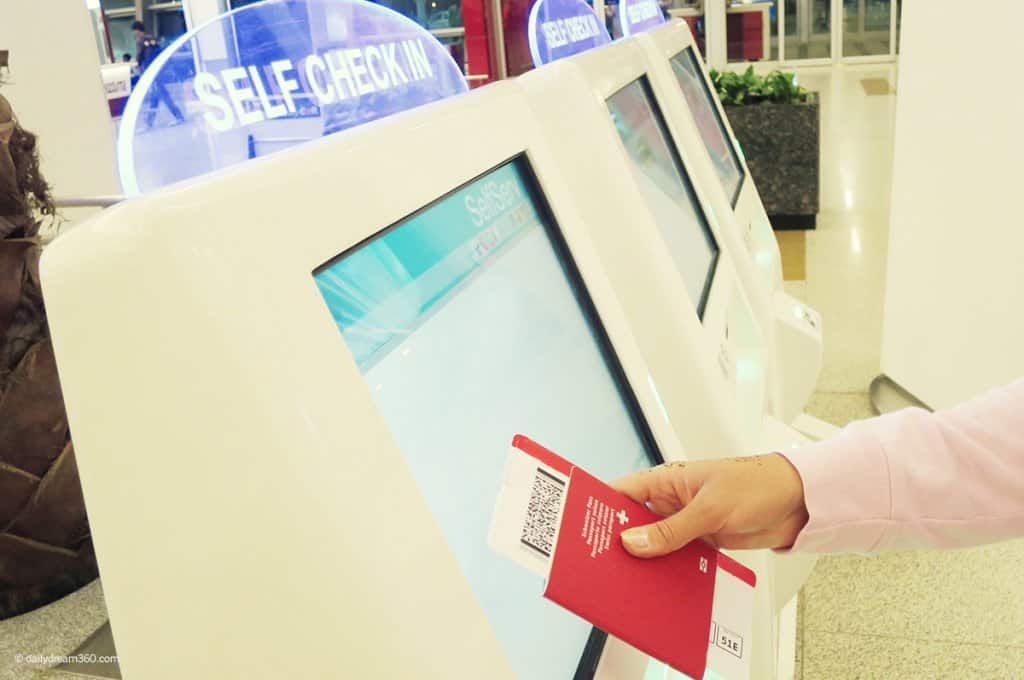 Person touching airport check-in machine