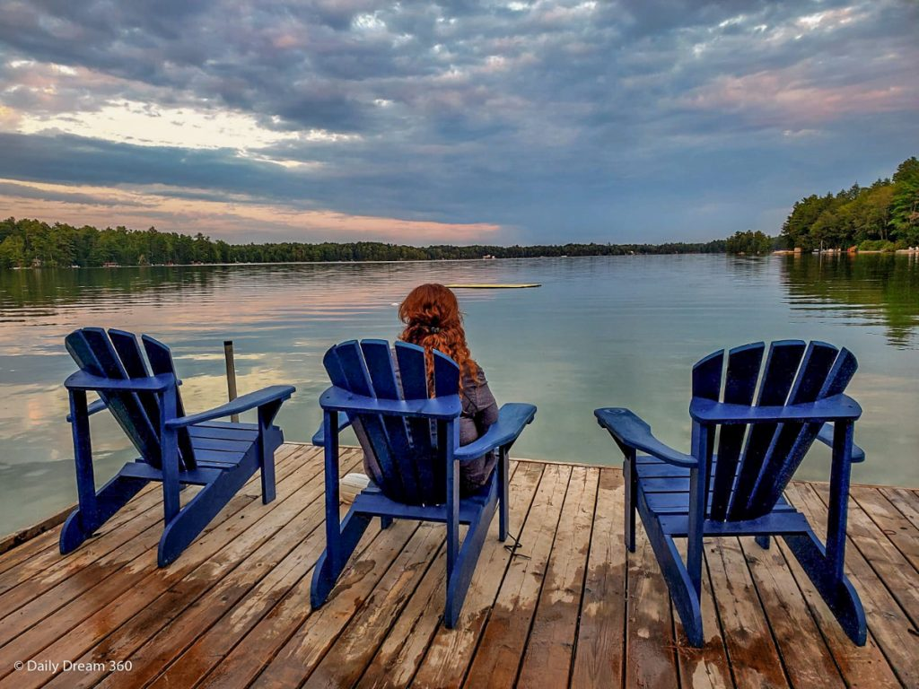 Girl sitting on Adirondack chair on dock over looking the lake at Muskoka Beer Spa