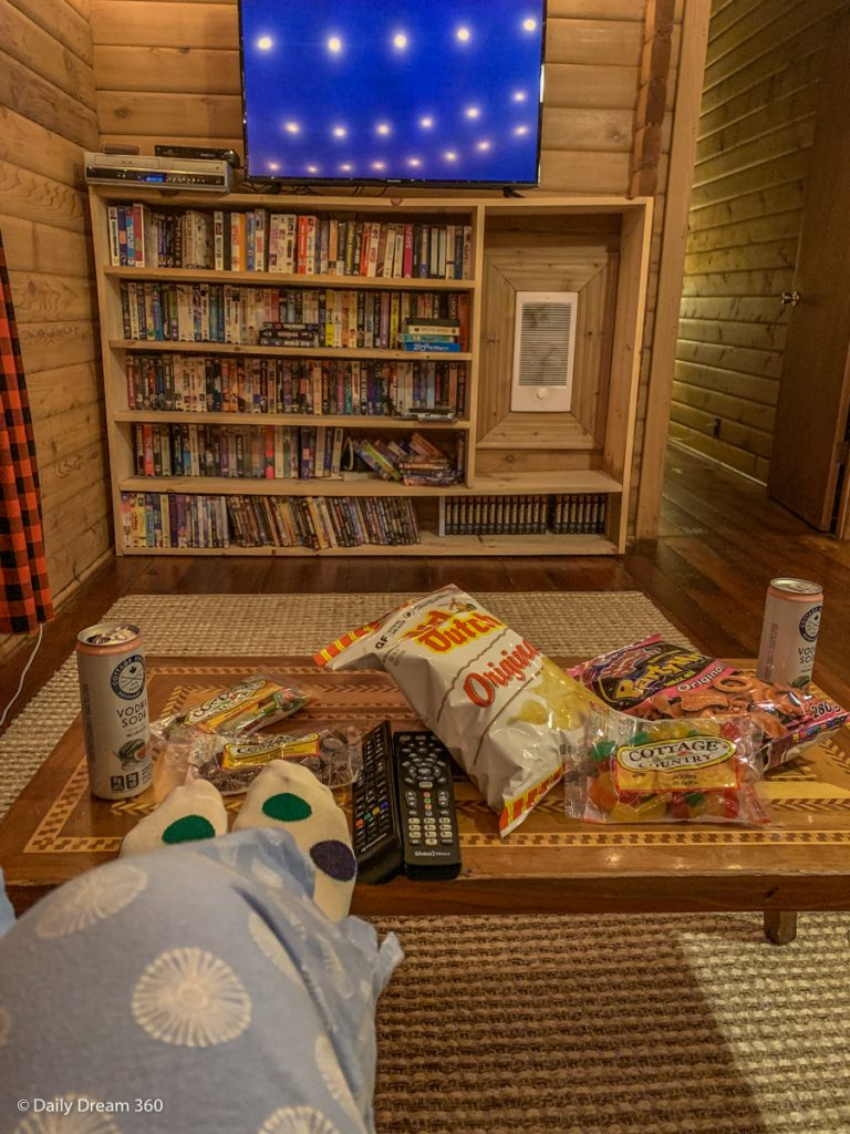 Feet in front of coffee table filled with snacks in front of TV and Video library at Muskoka Beer spa