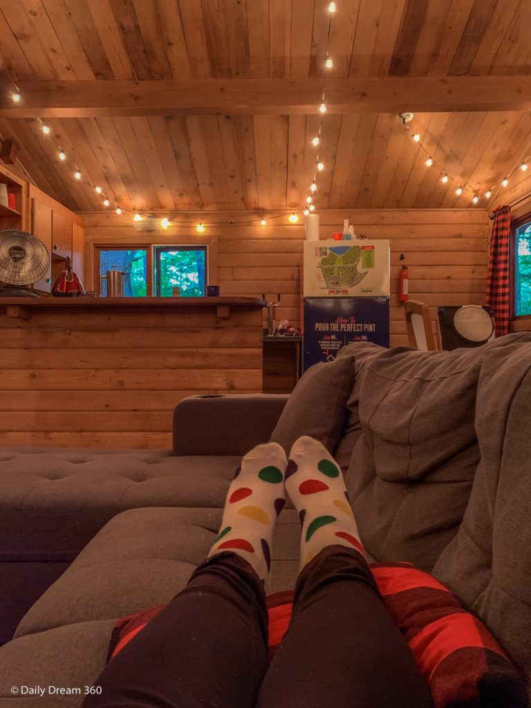 Woman sitting on couch looking into kitchen at Muskoka Beer Spa