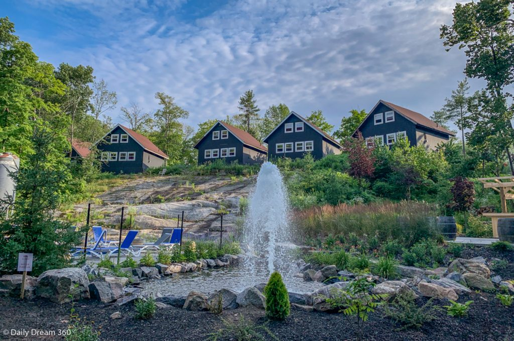 Muskoka Beer Spa Review - Cabins on hill top with water fountain in front