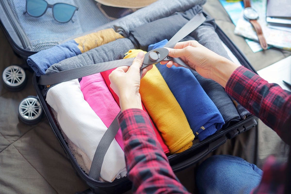women closing straps on suitcase with rolled clothing
