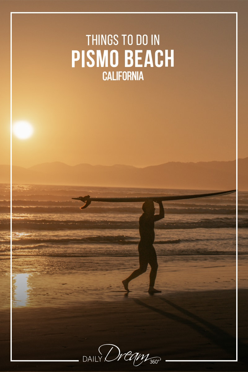 Surfer walks as sunsets behind him at Oceano Dunes Beach CA