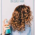 Girl with MoroccanOil products in her hands spraying curly hair