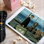 Tablet, popcorn and remote with text List of Travel Inspiration Movies That Will Inspire You to Travel