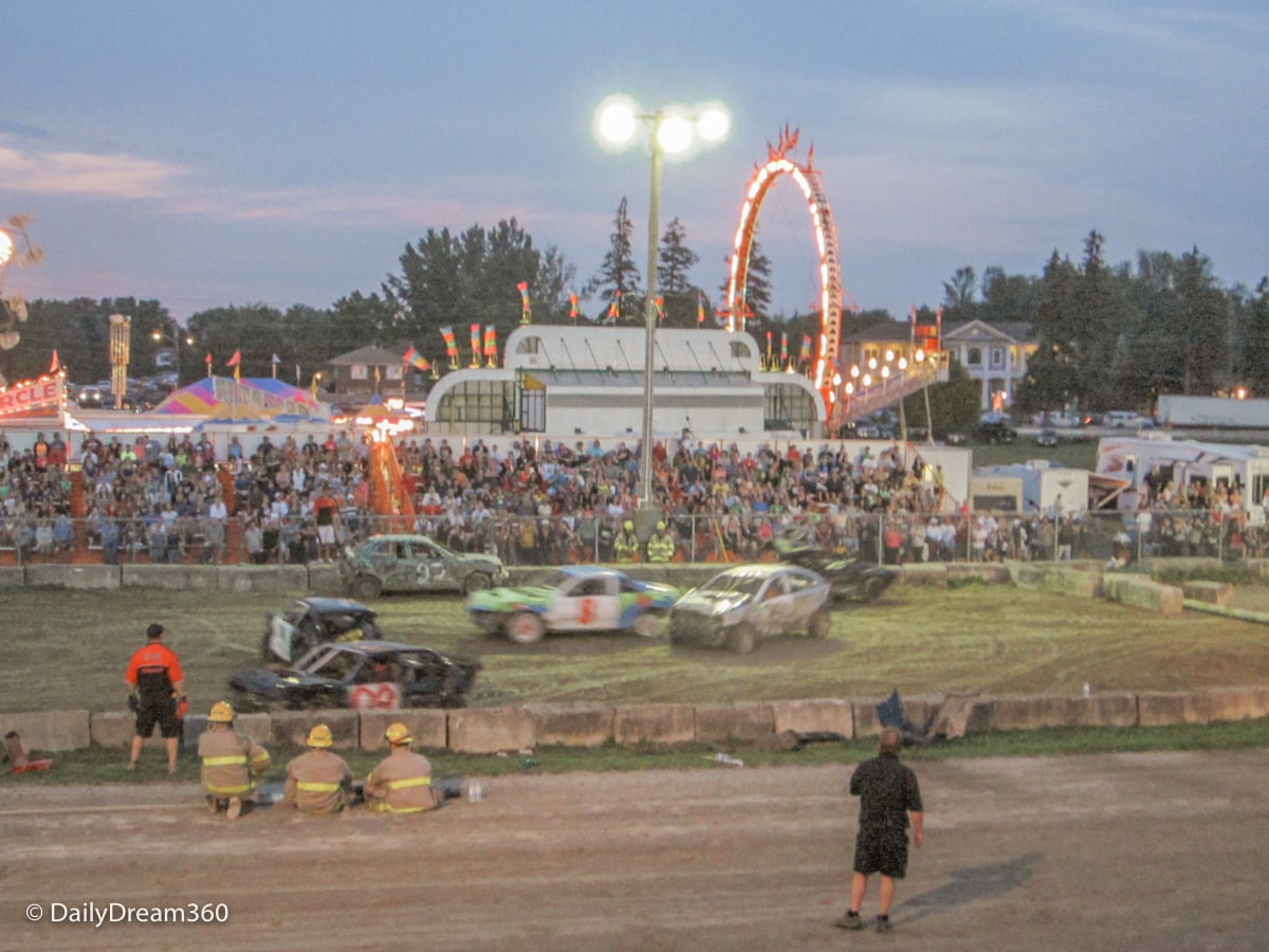 Demolition Derby with midway behind it at Port Perry Agricultural Fair