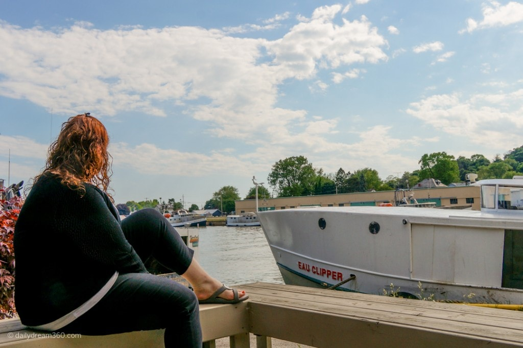 Sharon sitting on waterfront looking at fishing village Port Stanley Ontario Elgin County