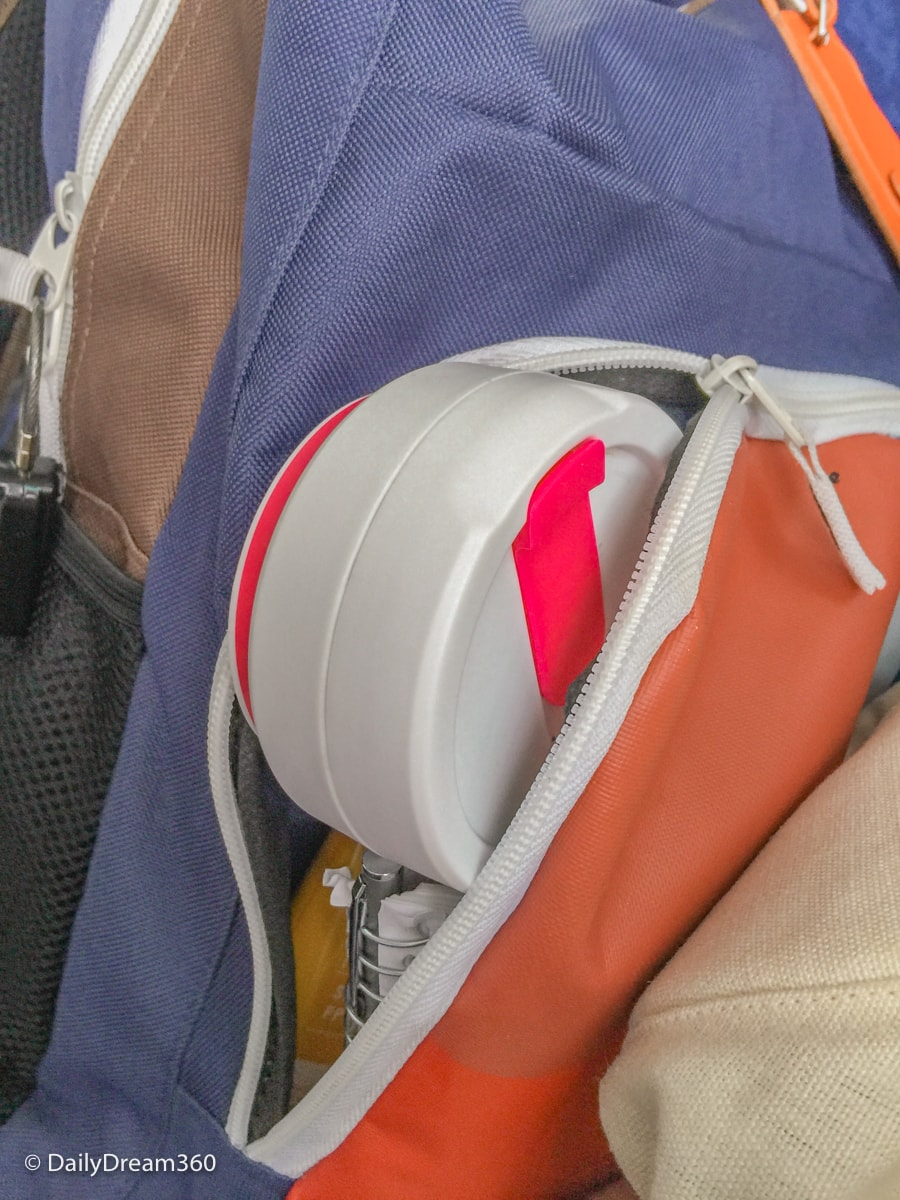 collapsed stojo pocket cup inside small backpack pocket