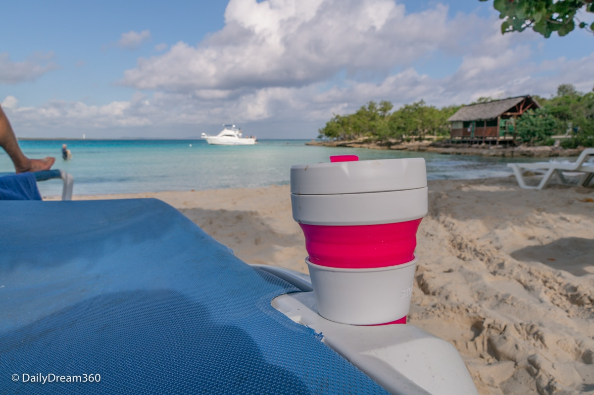stojo cup inside cup holder of sun chair on beach