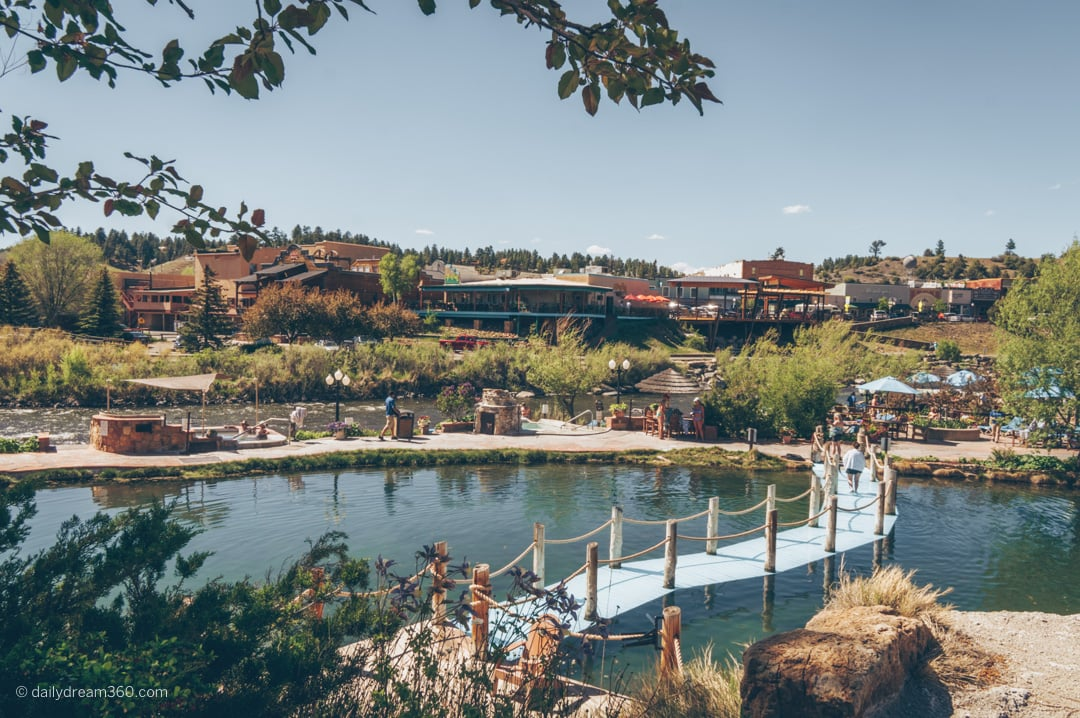Blue bridge sneaks across mineral pool and wide angle look at Pagosa Springs hot springs