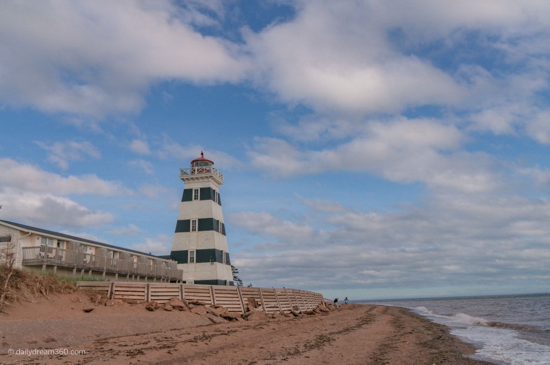 West Point Lighthouse on the beach as waves hit the shore in PEI