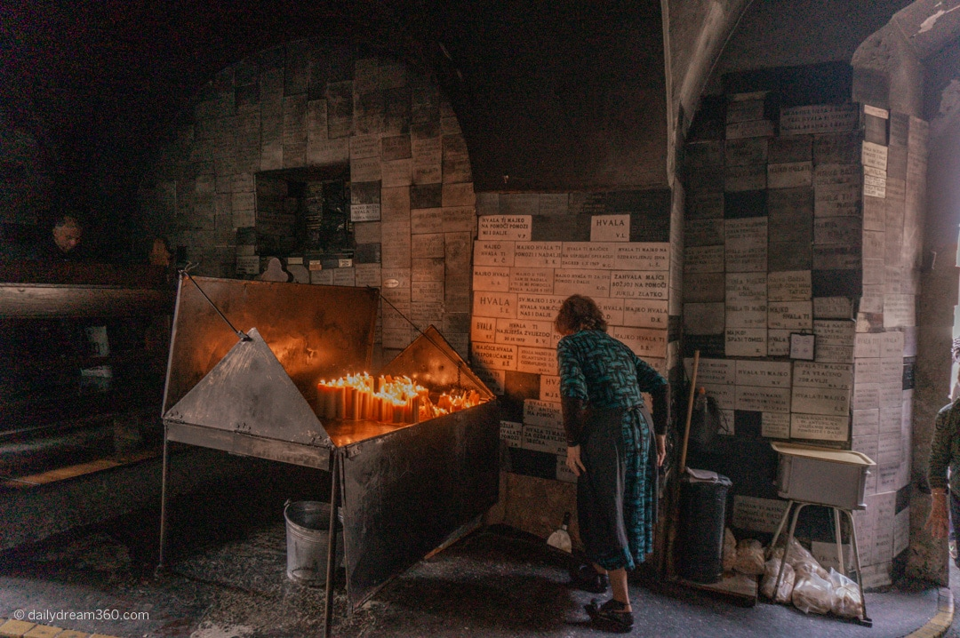 Woman reads bricks on wall in front of candle memorial at the Sacred Stone Gate in Zagreb Croatia